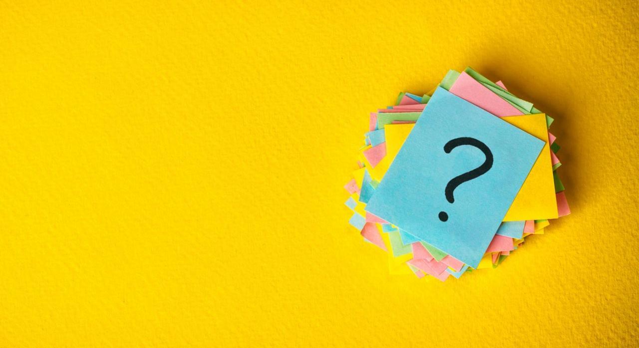 ICAC. Signos de interrogación escritos sobre amarillo de papel vintage