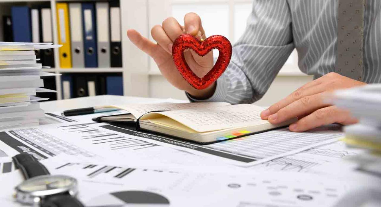 Razones por las que los contables aman su trabajo. Hombre frente a mesa llena de papeles sosteniendo en la mano un adorno con forma de corazón