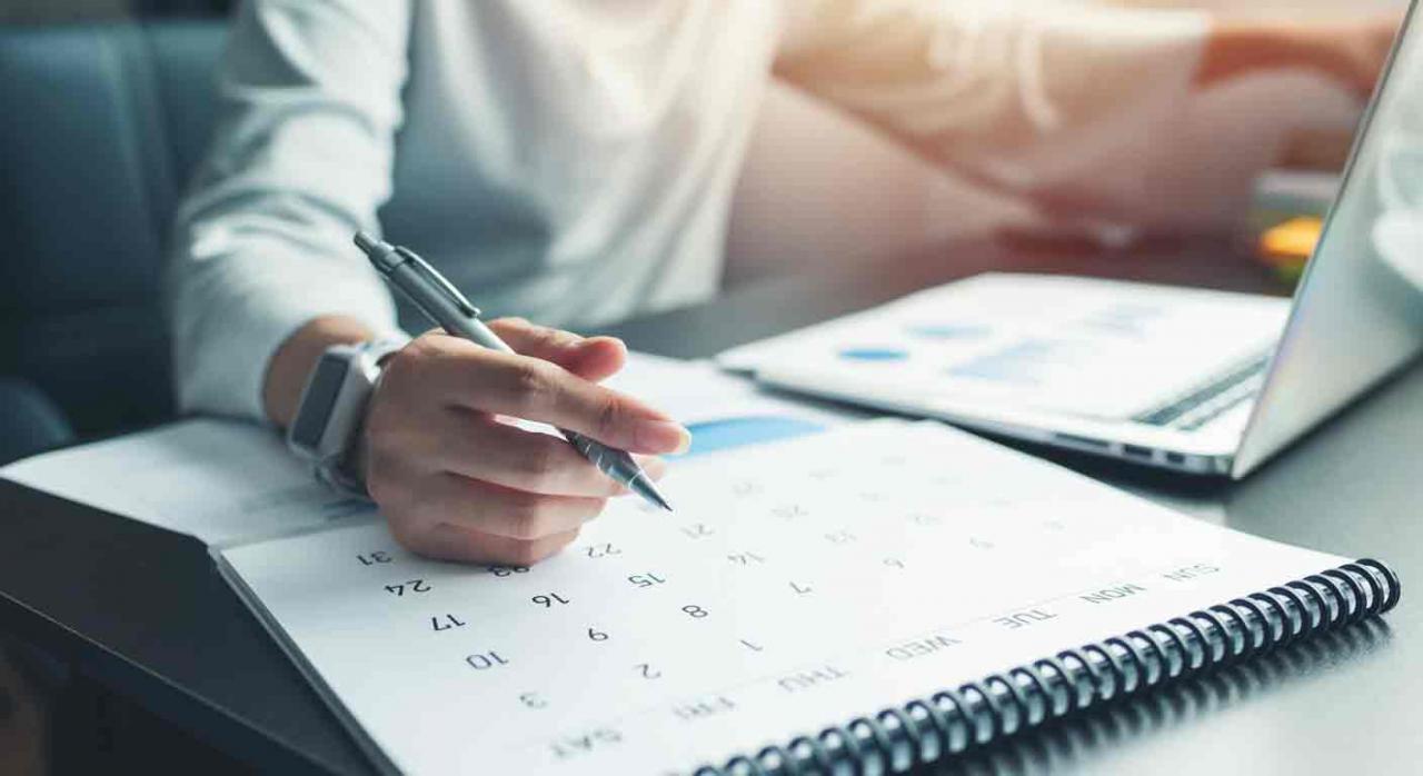 Ejercicio. Mujer con un portatil y señalando con un bolígrafo un día en un calendario