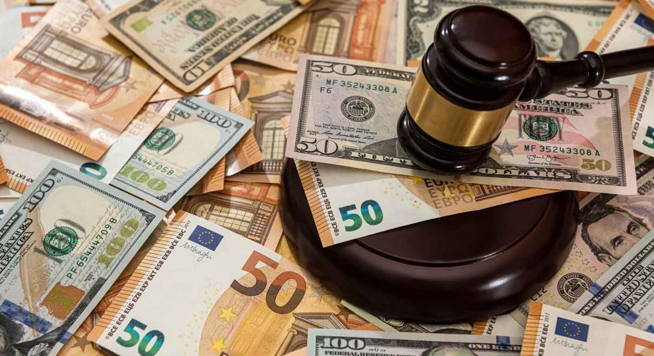 Montón de billetes de varios países y  el mazo de un juez