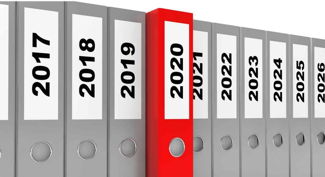 Carpetas grises de oficina ordenadas por años destacando en color rojo la del año 2020