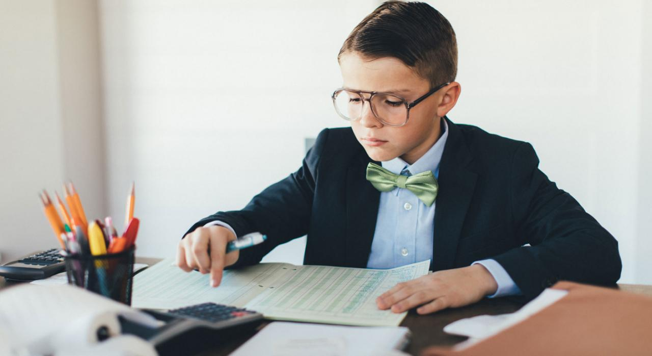 Conceptos básicos para introducirse en el mundo de la contabilidad. Imagen de un niño revisando una hoja de cuentas