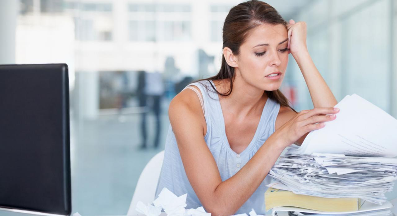 Indicadores que alertan de errores en la contabilidad. Mujer con gesto de preocupación frente a montaña de papeles