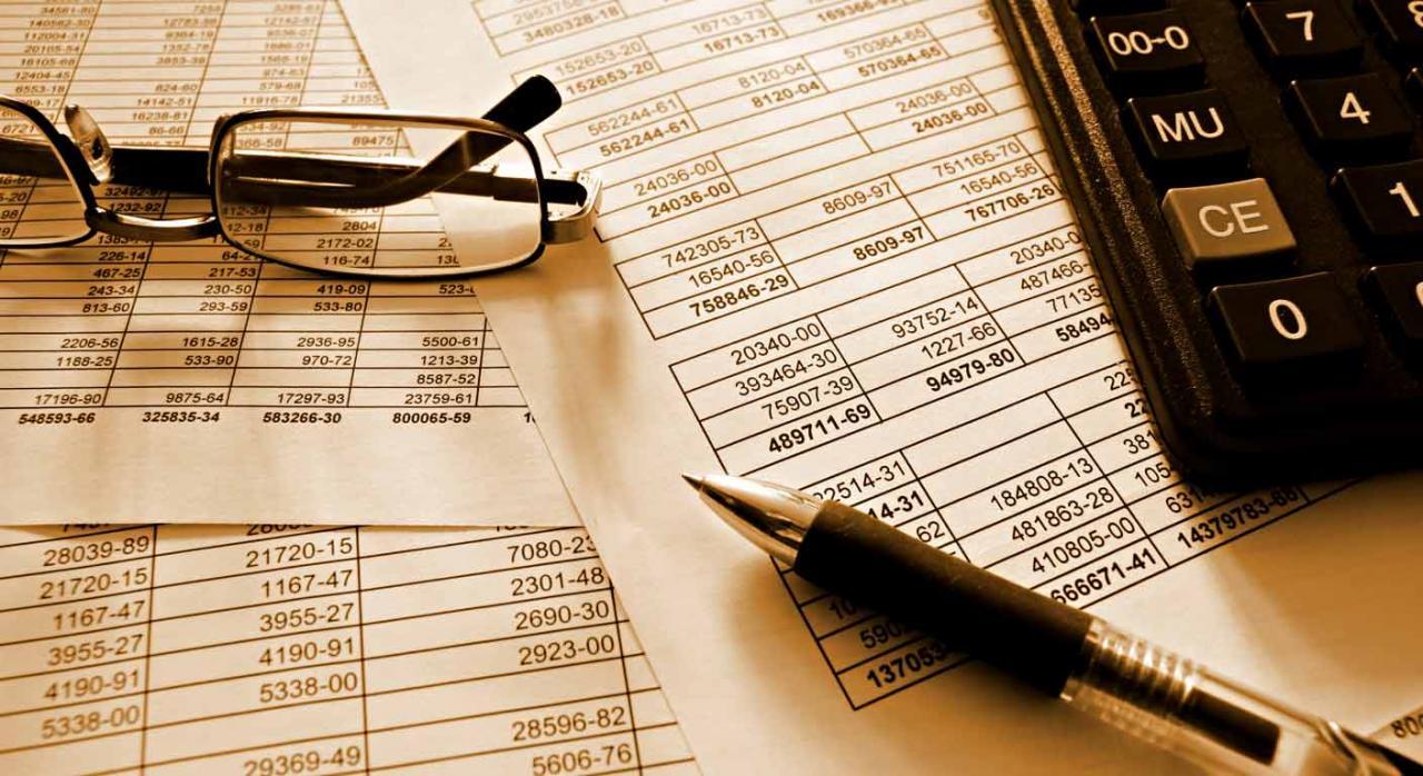Instrucción de contabilidad. Imagen de unas gafas, un bolígrado y una calculadora encima de documentos financieros
