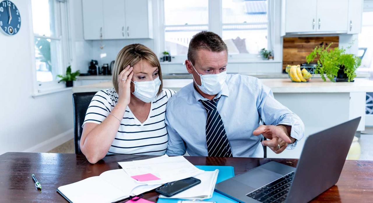 Necesidades financieras derivadas del COVID-19. Hombre y mujer con mascarilla mirando la pantalla de un ordenador