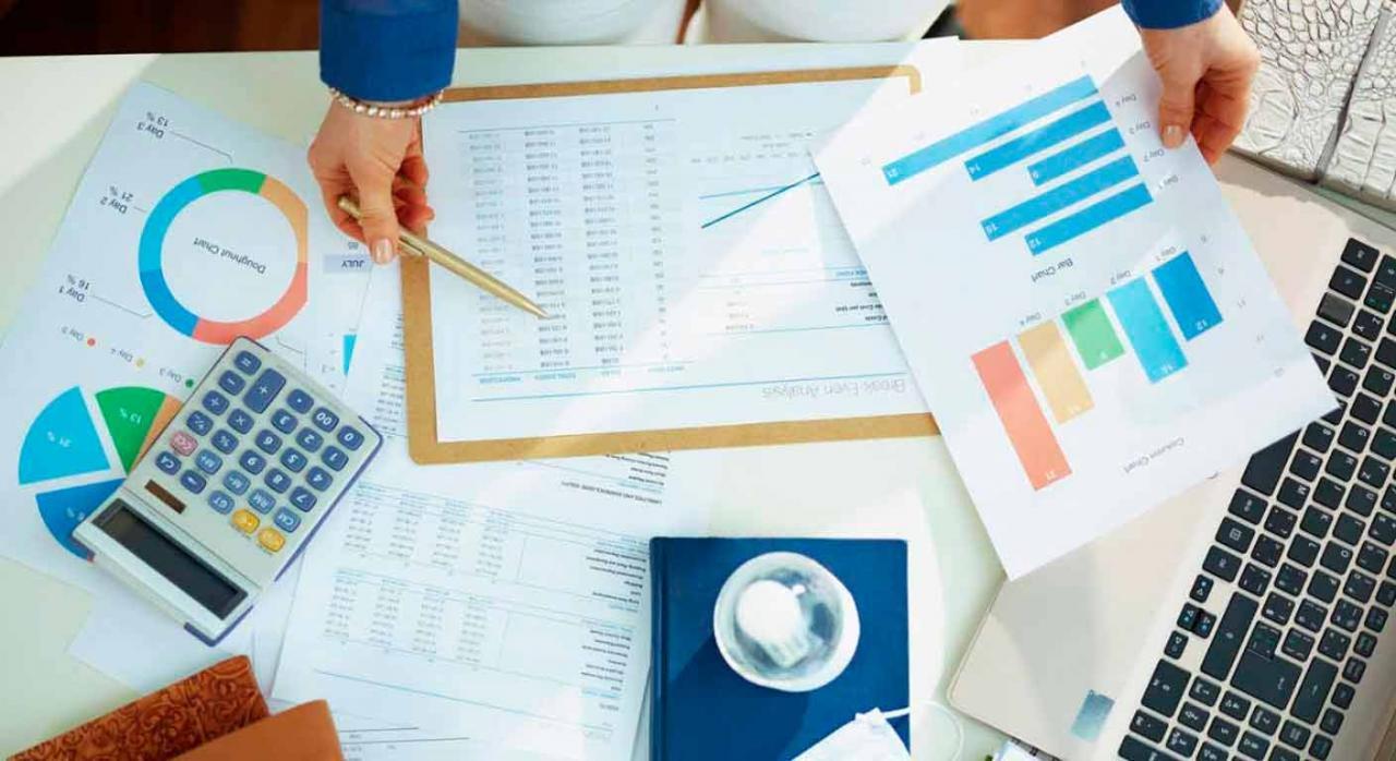 ERTE. Vista superior de mujer trabajado delante de una mesa llena de documentos