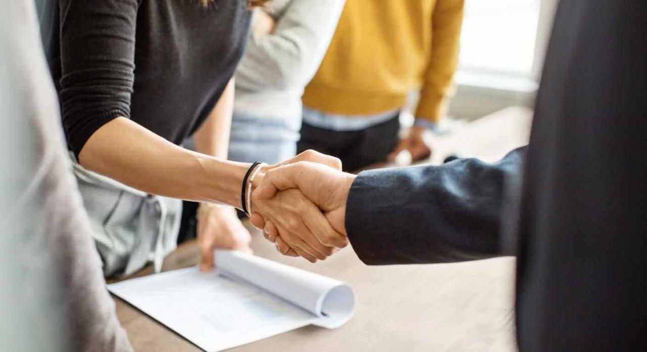 Dos personas de negocios estrechándose la mano en una oficina