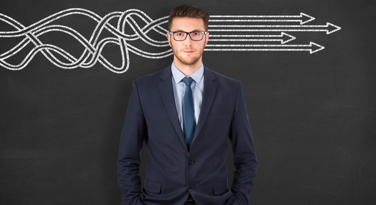 Empresario frente a una pizarra con unas flechas pintadas en blanco pensando sobre la mejorar de las habilidades directivas