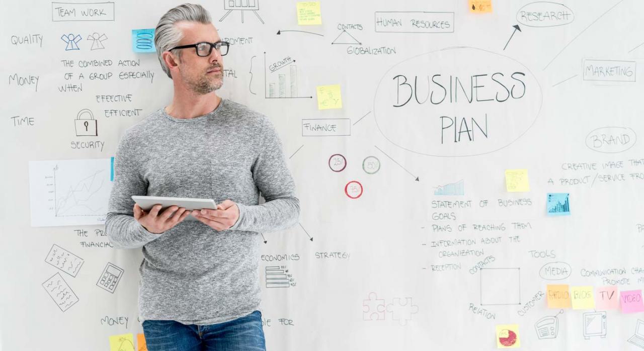 Hombre emprendedor con tablet y pizarra creando un business plan