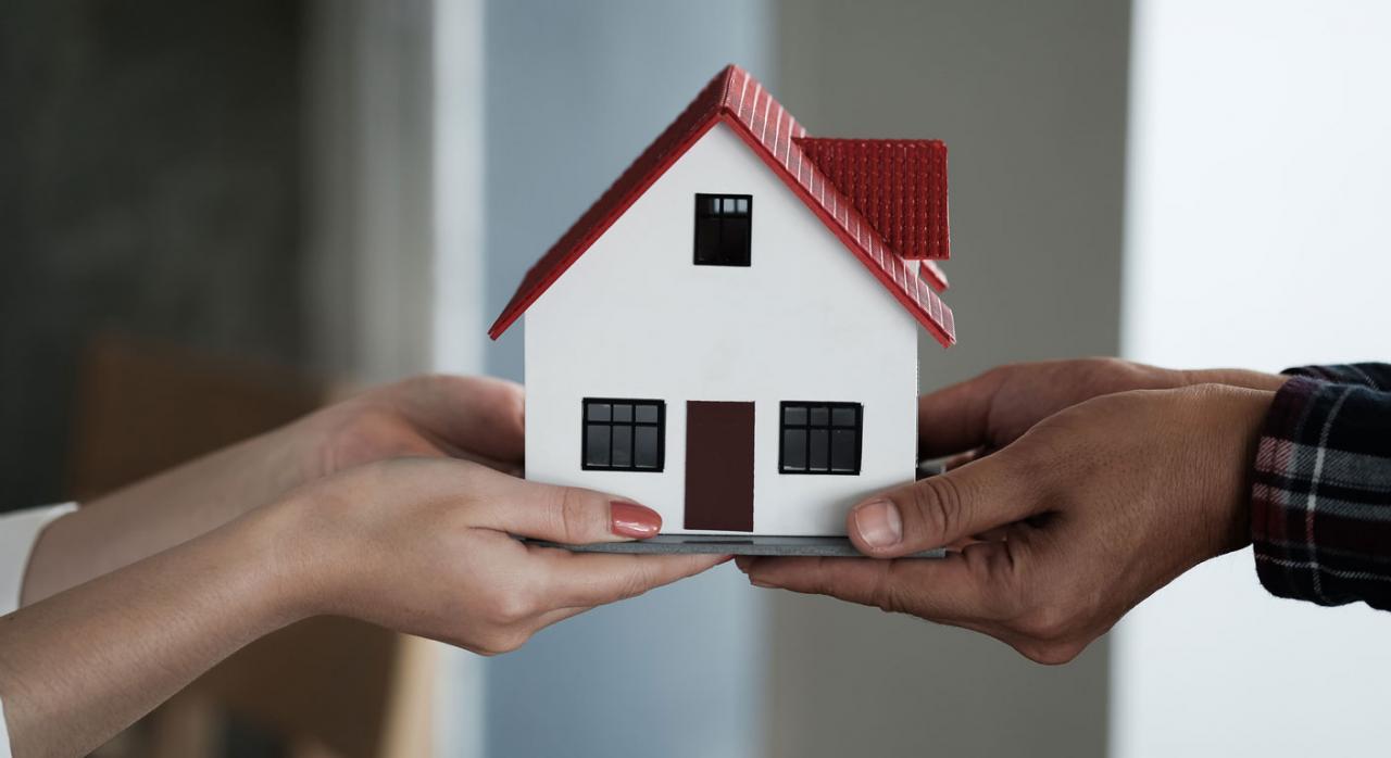 Como contabilizar el IVA en las donaciones de inmovilizado. Imagen de modelo de casa que sostienen en sus manos agente inmobiliario y cliente