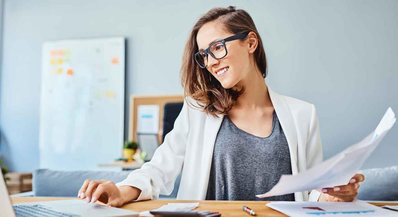 Contable. Mujer trabajando sonriente con su portátil y unos documentos