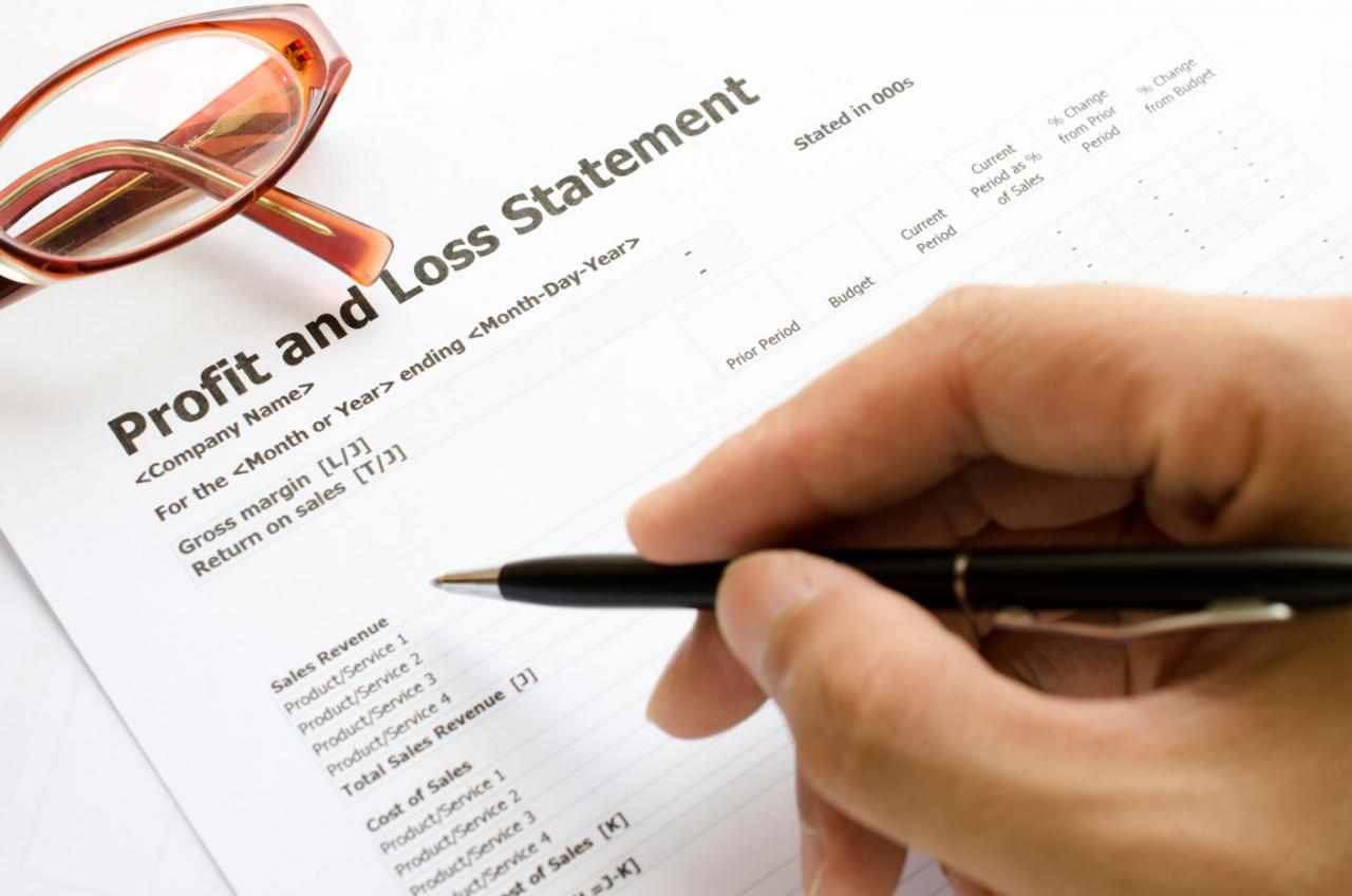 Claves para contabilizar un crédito por perdidas a compensar. Imagen de una mano con un bolii sobre un papel