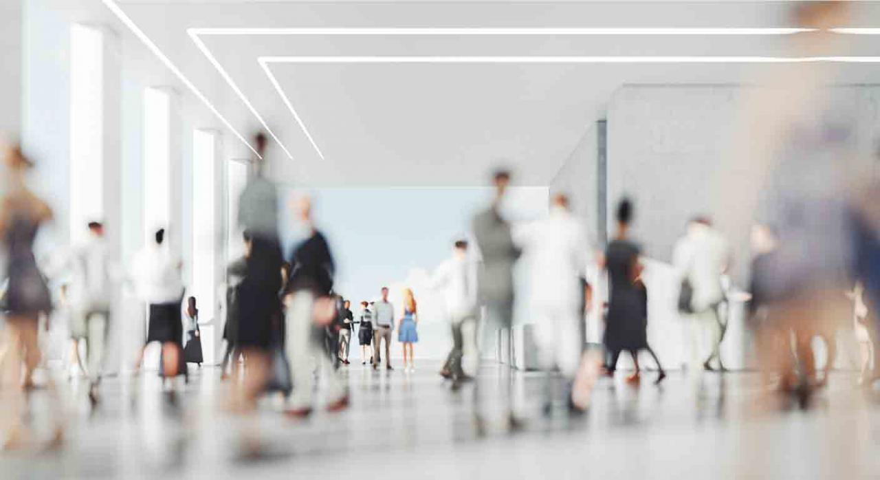 Clave descuento. Imagen de una sala con muchas personas desenfocadas andando en todas direcciones y una pareja la fondo enfocada