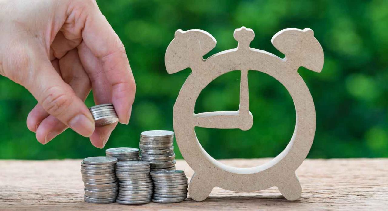 Inversión. Reloj despertador de madera y una mano haciendo una pila de monedas al lado