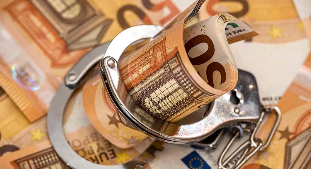 Riesgo de fraude y quiebra en Pymes. Fajo de billetes de 50 euros dentro de esposas