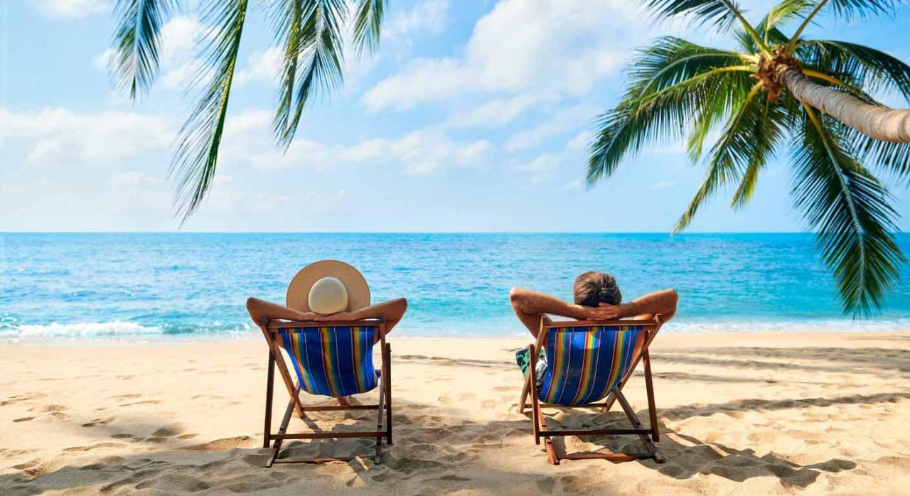 El trabajo del contable y las vacaciones. Imagen de pareja relajándose sentados en hamacas frente al mar